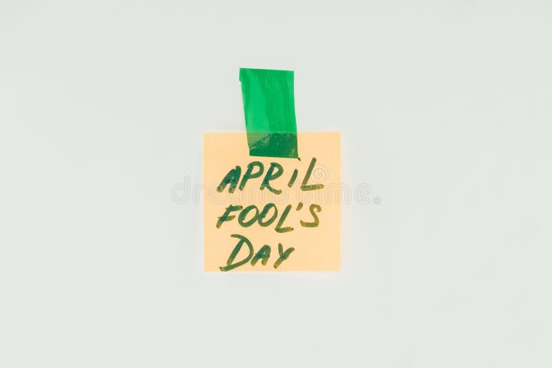 закройте вверх по взгляду примечания при литерность дня дурачков в апреле и липкая лента изолированные на сером цвете, концепции  стоковое фото