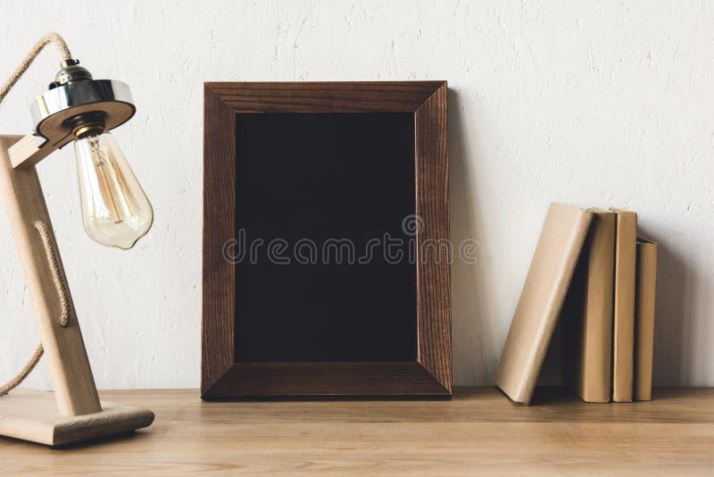 закройте вверх по взгляду пустых рамки и настольной лампы фото стоковая фотография rf