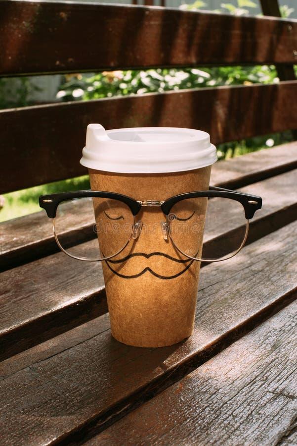 закройте вверх по взгляду устранимой чашки с знаком и eyeglasses усика стоковое фото