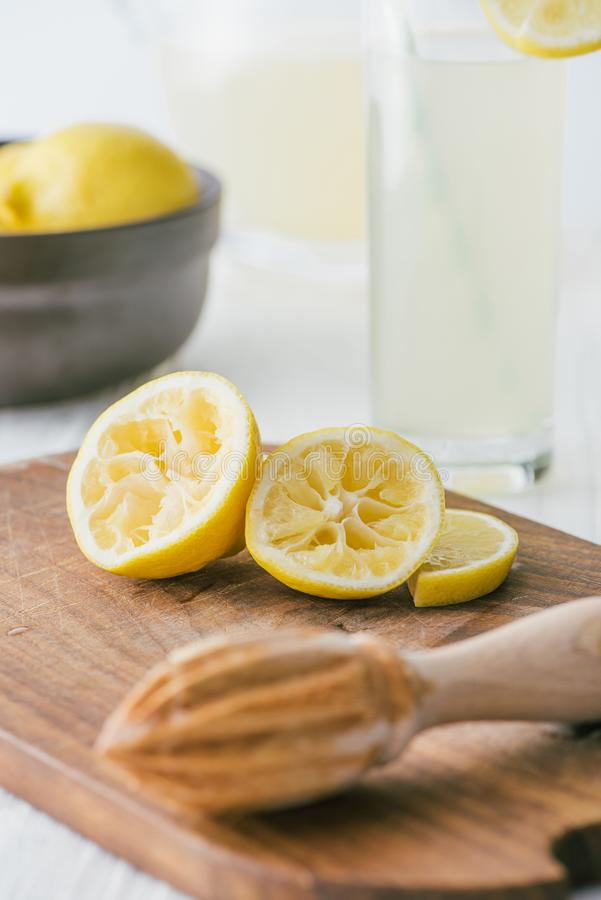 закройте вверх по взгляду частей лимона и деревянного squeezer на разделочной доске для делать лимонад стоковые фотографии rf