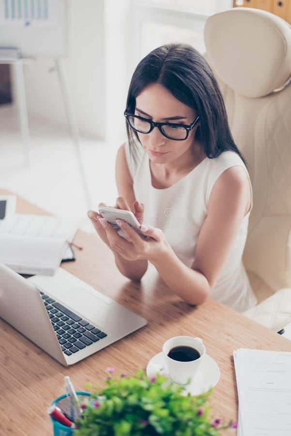Закройте вверх по взгляд сверху молодой печатать женщины брюнет sms на ее p стоковое изображение