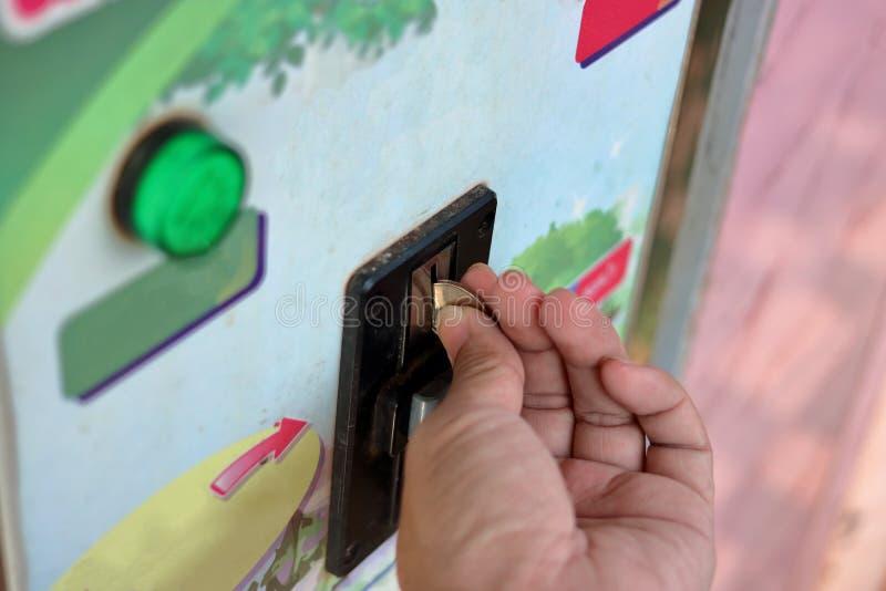 Закройте вверх по взгляду руки человеческой вводя монетки внутри к старому торговому автомату, малой глубине поля, автоматической стоковые изображения