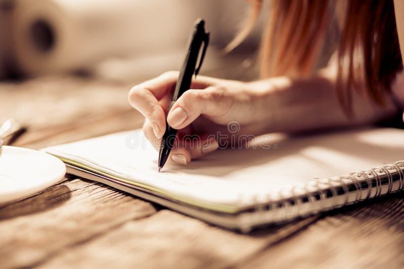 Закройте вверх по взгляду сочинительства руки женщины с ручкой на тетради на деревянном столе стоковое изображение rf
