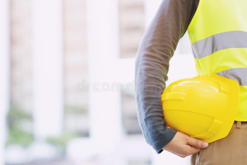 Закройте вверх по - виду спереди проектировать мужскую стойку рабочий-строителя держа безопасность стоковая фотография rf