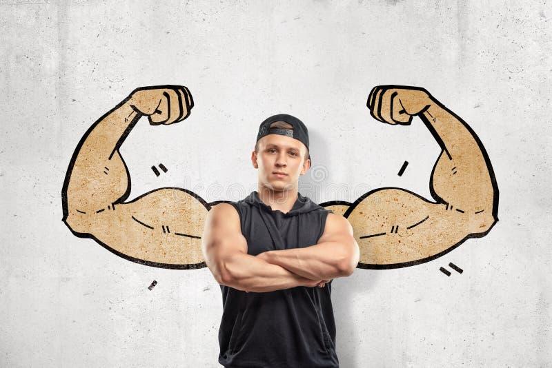 Закройте вверх по - вид спереди молодого атлетического человека с оружиями пересек, стоящ против стены с чертежом больших мышечны стоковая фотография rf