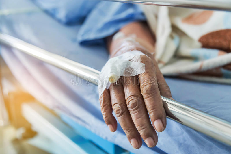 Закройте вверх по внутривенному катетеру для впрыски заткните внутри руку пожилого пациента стоковое изображение