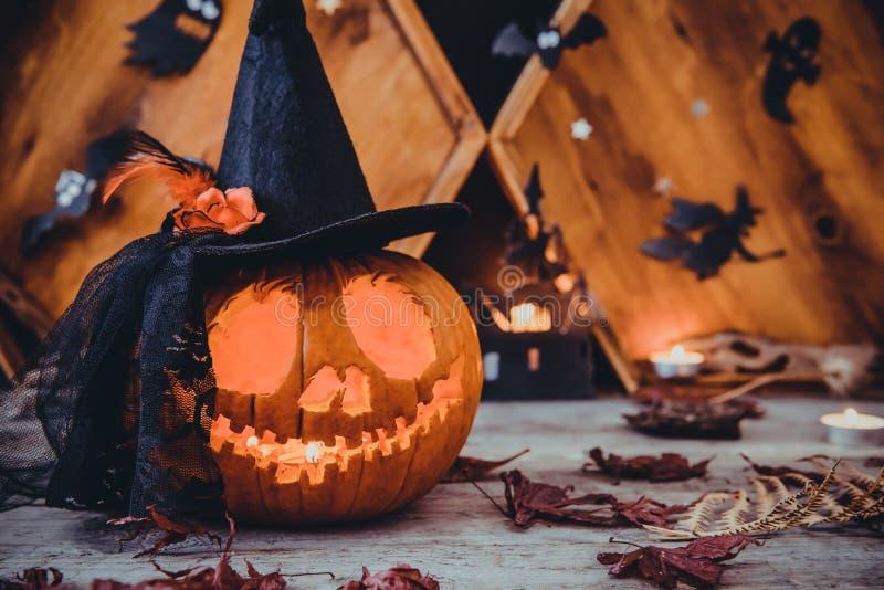 Закройте вверх по высекаенной тыкве в шляпе ведьмы с бумажными силуэтами летучих мышей, замку, призракам на деревянной предпосылк стоковые фото