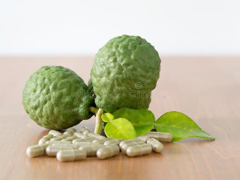 Закройте вверх по группе в составе свежий бергамот с зелеными листьями и зеленая капсула на деревянном столе преимущества бергамо стоковые изображения