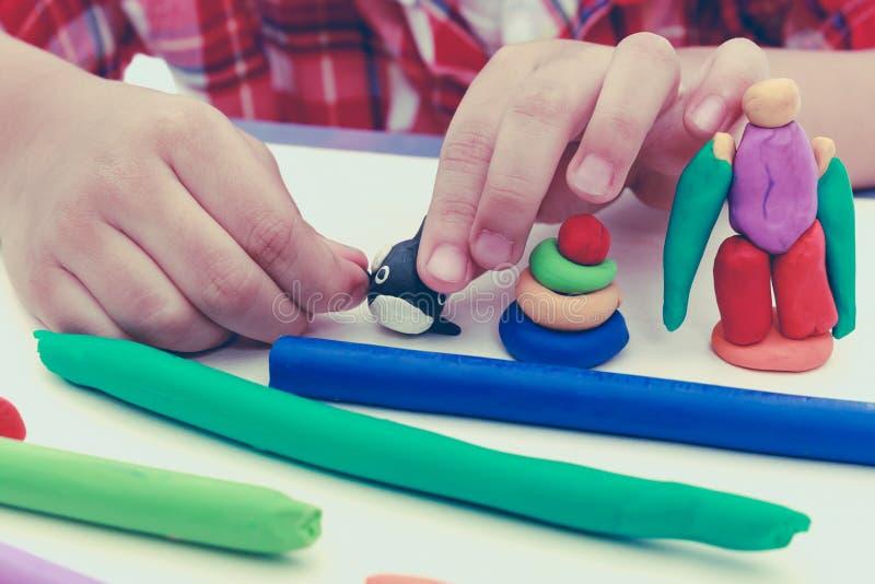 Закройте вверх по глине моделирования руки ребенка отливая в форму Усильте ima стоковые изображения