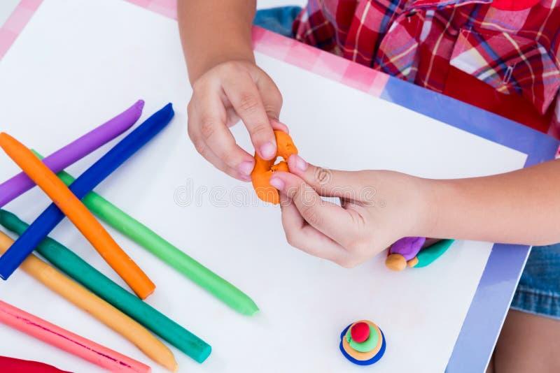 Закройте вверх по глине моделирования руки ребенка отливая в форму Усильте ima стоковая фотография rf