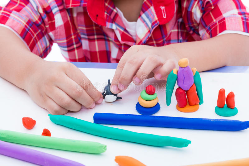 Закройте вверх по глине моделирования руки ребенка отливая в форму Усильте ima стоковое фото rf