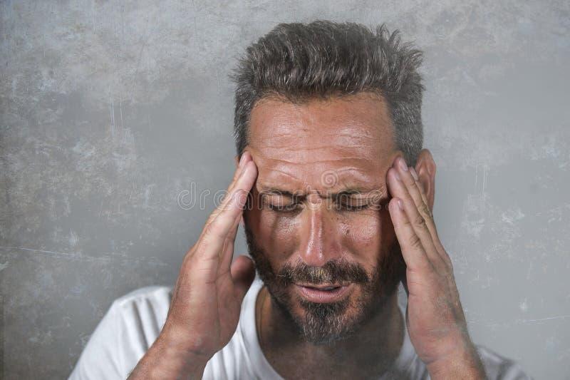 Закройте вверх по драматическому портрету молодого привлекательного встревоженного и подавленного человека в боли с руками на его стоковое изображение rf