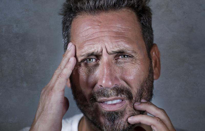 Закройте вверх по драматическому портрету молодого привлекательного встревоженного и подавленного человека в боли с руками на его стоковое фото rf