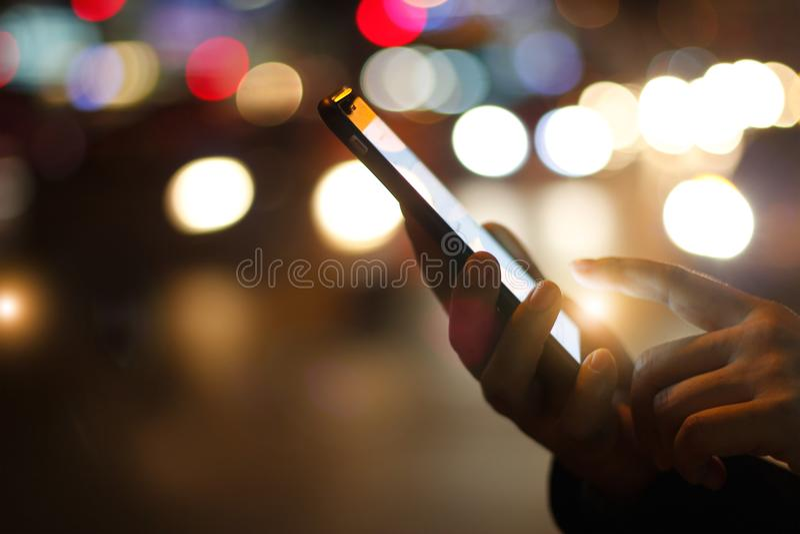 Закройте вверх по женским рукам используя передвижной smartphone в загоренном col стоковые изображения rf
