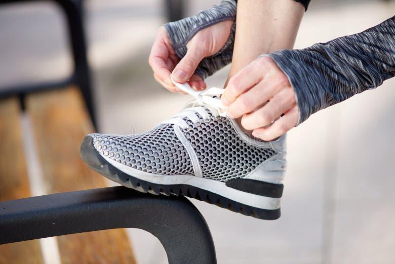 Закройте вверх по женской руке связывая шнурок стоковое изображение