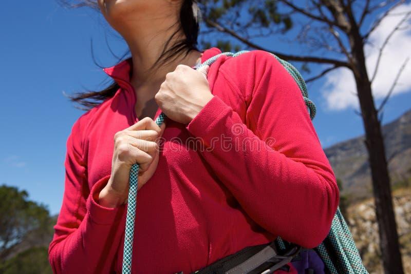 Закройте вверх по женскому альпинисту держа моток веревочки outdoors стоковое изображение