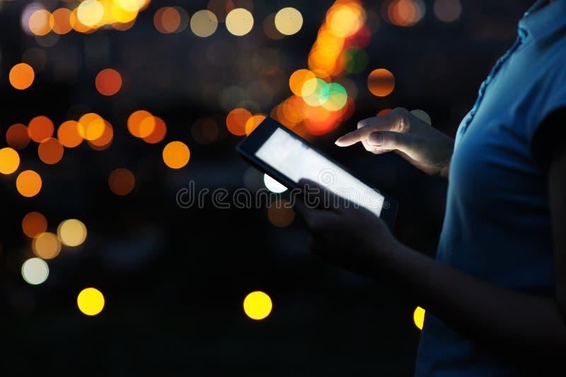 Закройте вверх по женщине используя цифровую таблетку в ноче стоковое фото rf
