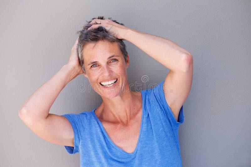 Закройте вверх по женщине постаретой серединой смеясь над с руками в волосах стоковое изображение rf