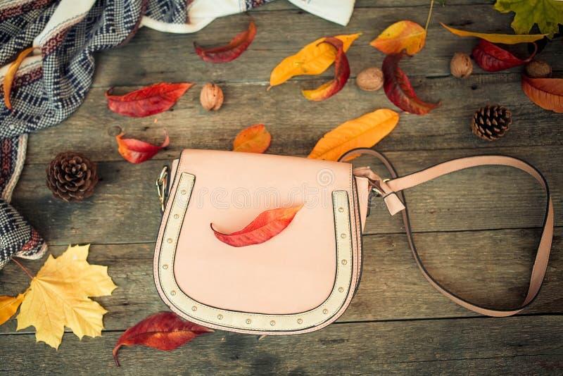 Закройте вверх по женщины листья сумки и осени на деревянной предпосылке стоковое фото
