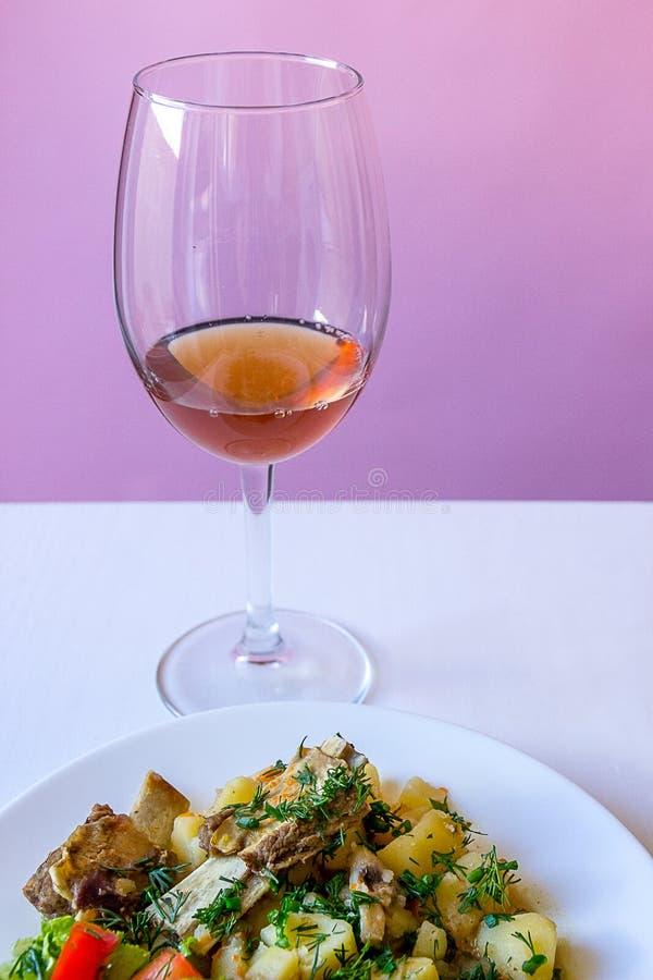 Закройте вверх по заполненным картошкам с нервюрами телятины и свежими салатом и стеклом розовой лозы стоковая фотография