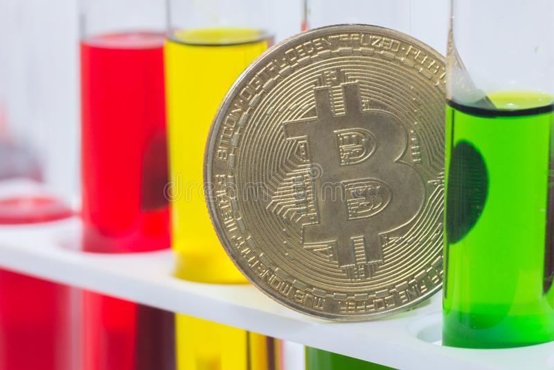Закройте вверх по золотому bitcoin с жидкостью в трубке стоковая фотография