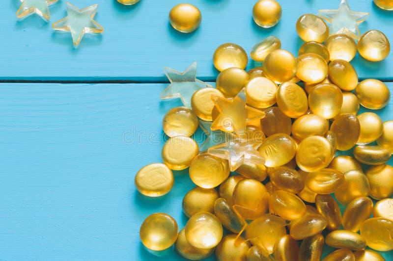 Закройте вверх по изображению желтых мраморов на голубой деревянной предпосылке стоковое фото rf
