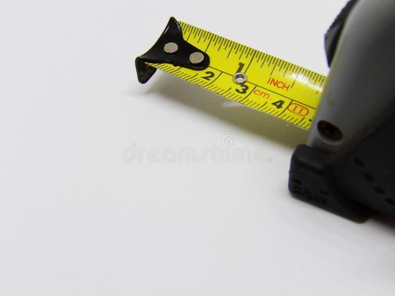 Закройте вверх по изображению макроса workmans измеряя ленту для проверять расстояния стоковое изображение rf