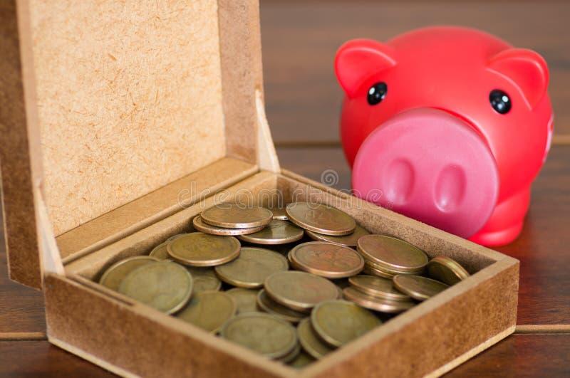 Закройте вверх по коричневой коробке заполненной с монетками доллара, розовой копилке сидя рядом с ей стоковая фотография rf
