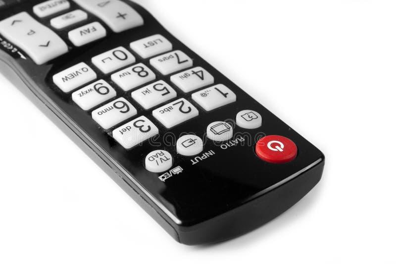 Закройте вверх по красной кнопке силы на изолированном дистанционном управлении ТВ стоковые изображения