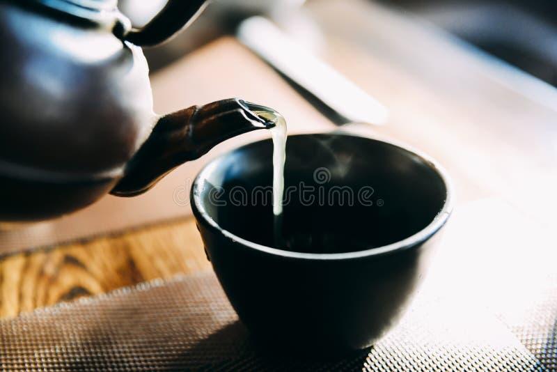 Закройте вверх по лить горячий японский зеленый чайник на восточной чашке стиля на таблице стоковые изображения rf