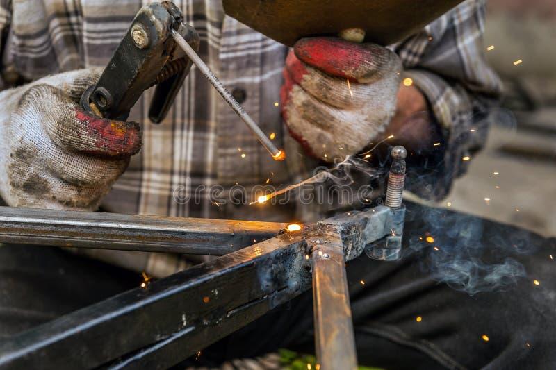 Закройте вверх по макросу заварки в мастерской, мужском сварщике используя электрод стоковые фото