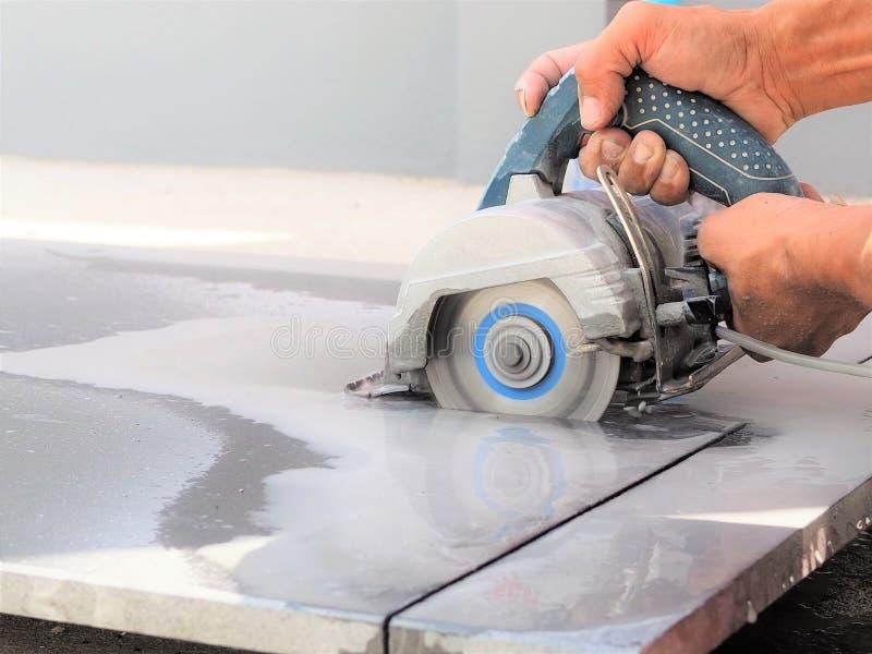 Закройте вверх по машине sawing пользы работника влажной для резать мраморный камень стоковые изображения rf