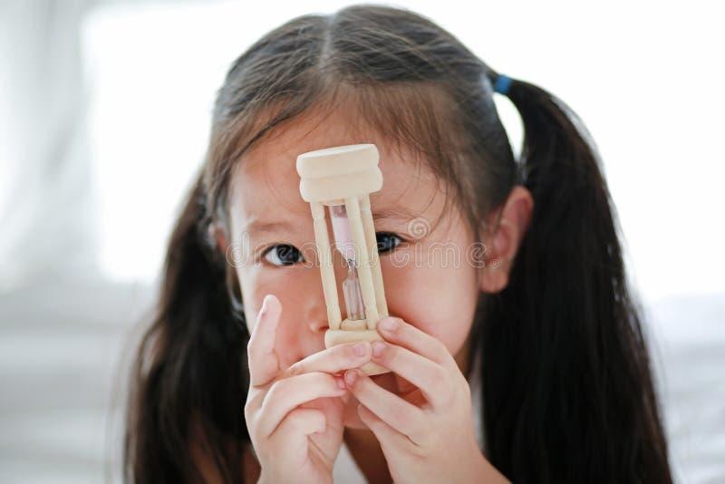 Закройте вверх по меньшей азиатской девушке держа sandglass в руке со смотреть через камеру Времена ожидания с часами стоковые фотографии rf