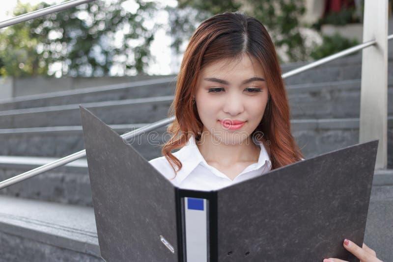 Закройте вверх по молодой азиатской бизнес-леди смотря бумагу документа на связывателе кольца стоковое изображение rf