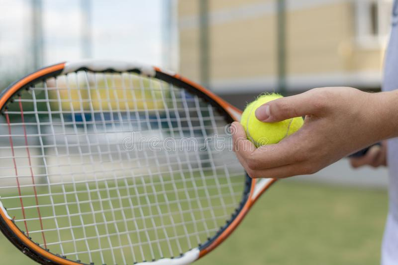 Закройте вверх по молодому человеку держа теннисный мяч и ракетку стоковые фото