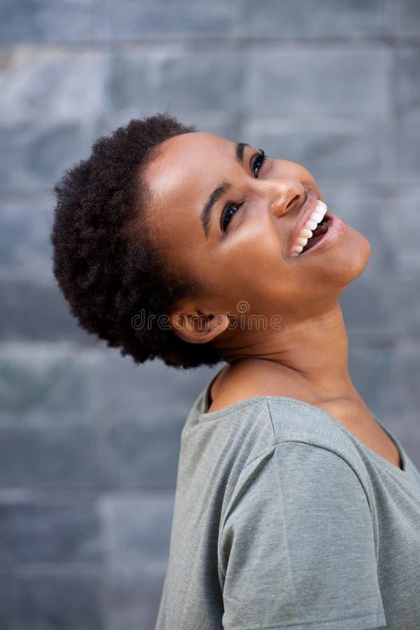 Закройте вверх по молодой африканской женщине смеясь над и смотря вверх стоковое изображение rf