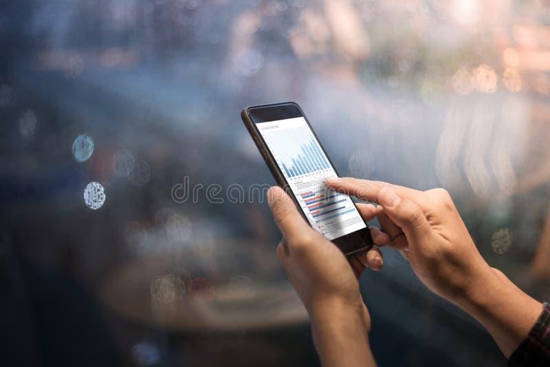 Закройте вверх по мужским рукам держа smartphone с диаграммой диаграммы стоковое фото