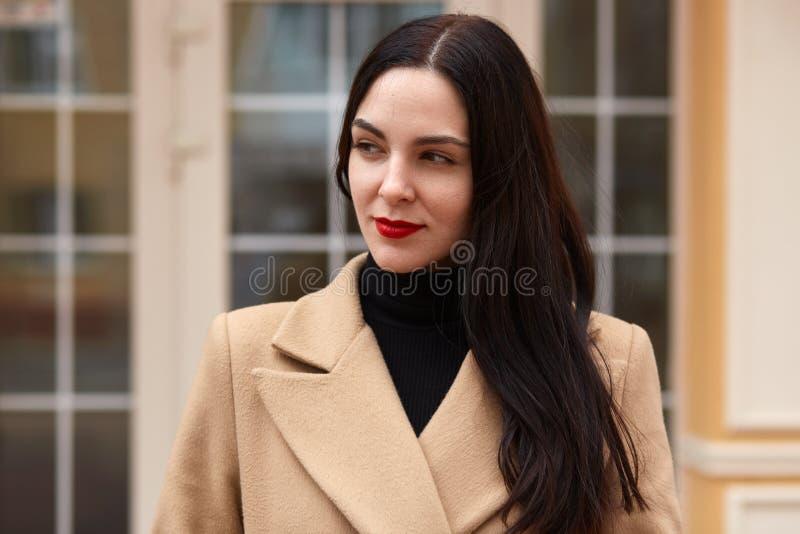 Закройте вверх по на открытом воздухе портрету молодой красивой стильной девушки в бежевом пальто и черный свитер, имеет длинные  стоковое фото rf