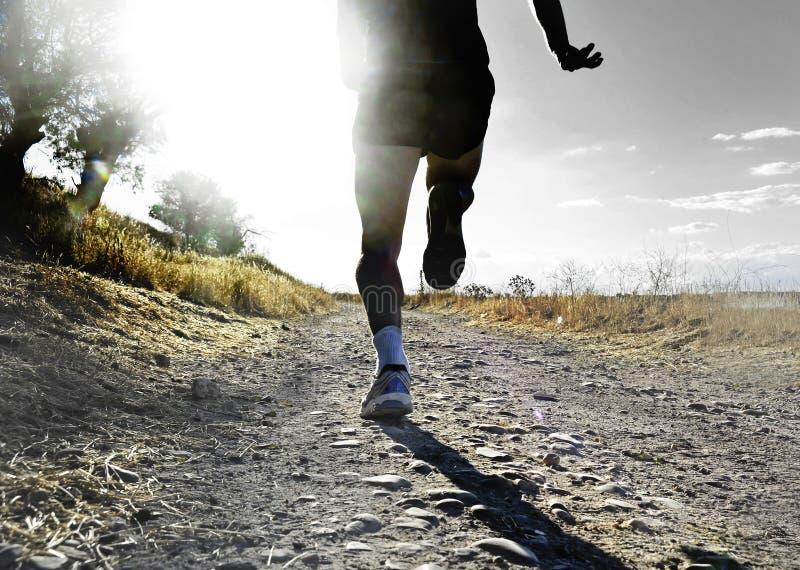 Закройте вверх по ногам и ногам весьма хода и тренировки человека по пересеченной местностей на сельском следе jogging на заходе  стоковая фотография rf
