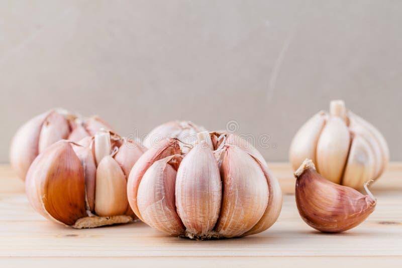 Закройте вверх по органическому чесноку с селективным фокусом на древесине teak стоковые фото