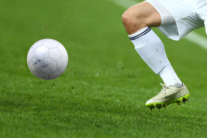 Закройте вверх по одной ноге и ногам футболиста с шариком стоковое фото rf