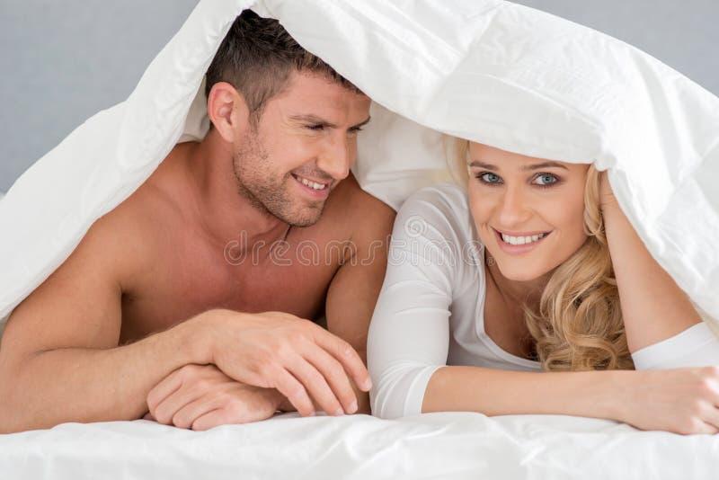 Закройте вверх по парам среднего возраста романтичным на кровати стоковые фото
