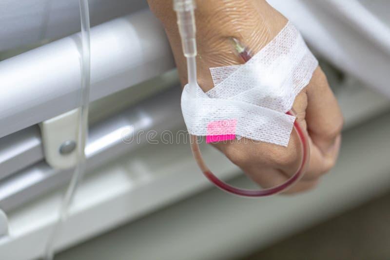 Закройте вверх по пациенту женщины руки с впрыской соляной в руке и во время лежа кроватей реабилитации больница стоковое изображение rf