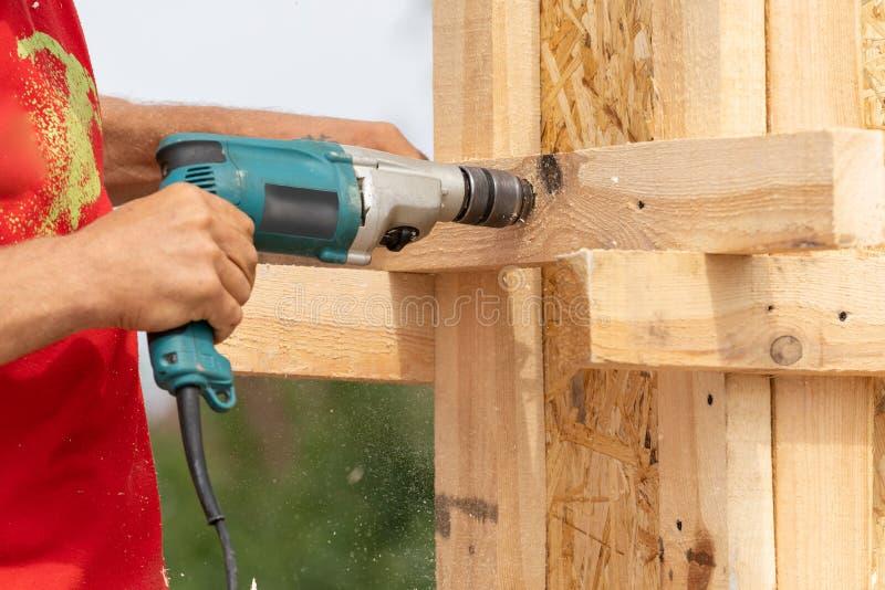 Закройте вверх по подрезанному фото рабочих классов используя доску планки удерживания сверла на деревянных конструкции поляка ил стоковые изображения rf