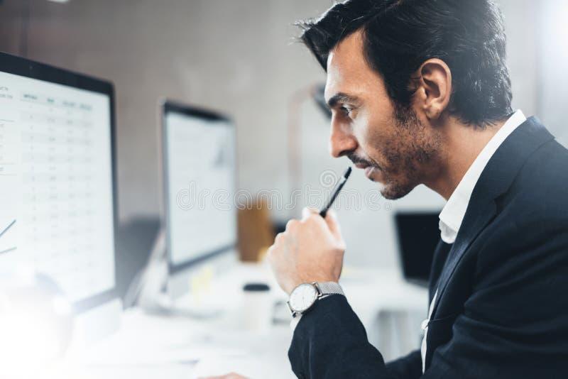 Закройте вверх по портрету бизнесмена работая на солнечном офисе на настольном компьютере пока сидящ на таблице запачканный стоковая фотография rf