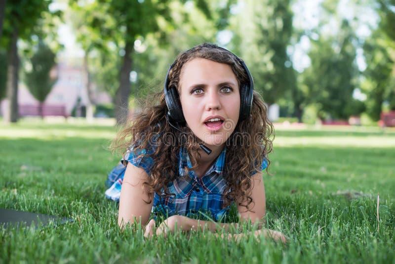 Закройте вверх по портрету лежать музыки милой маленькой девочки слушая стоковые изображения