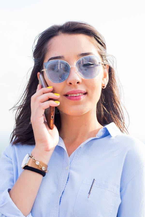 Закройте вверх по портрету красивой женщины брюнет говоря на smartphone на белой предпосылке стоковое фото