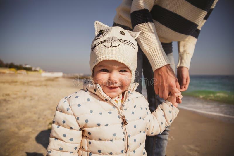 Закройте вверх по портрету маленького усмехаясь ребенка держа руку ` s матери outdoors на океане, смотря камеру стоковые изображения rf