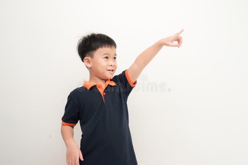 Закройте вверх по портрету милого мальчика указывая с пальцем в dist стоковое фото
