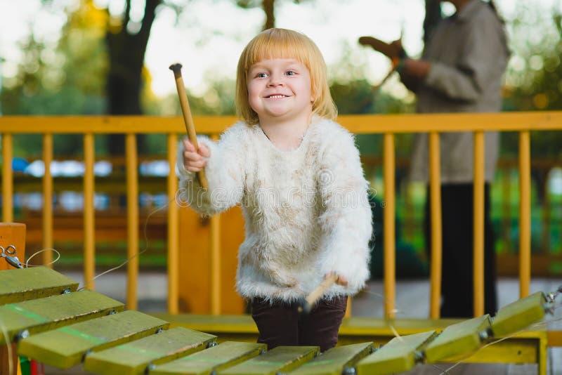 Закройте вверх по портрету милой девушки играя ксилофон внешний стоковые фото